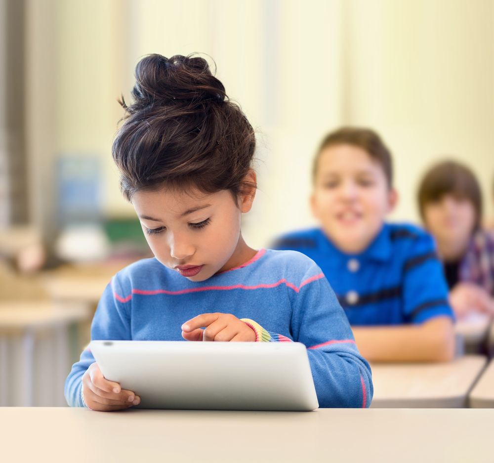 Little girl using tablet at school