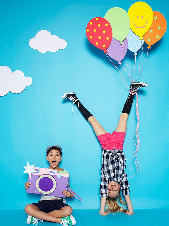 Boy holding giant paper camera next to girl doing handstand with bouquet of paper balloons tied to her foot