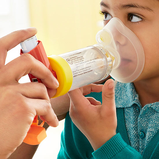 Child using inhaler spacer and mask
