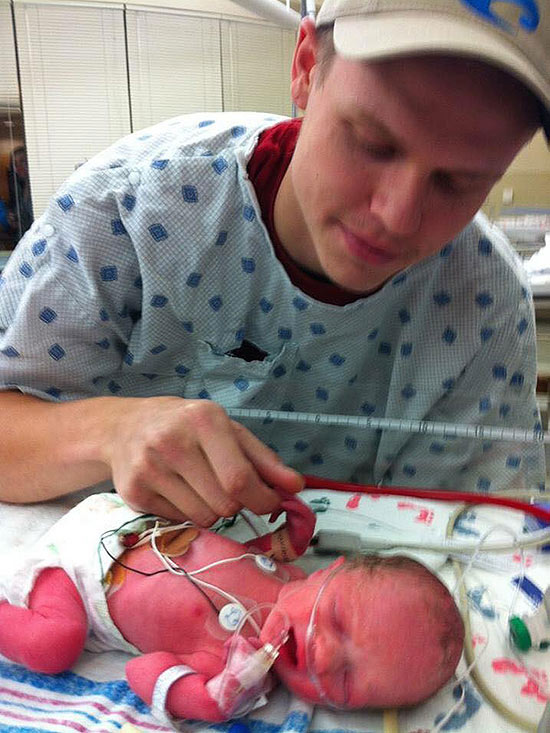 father looking at newborn baby