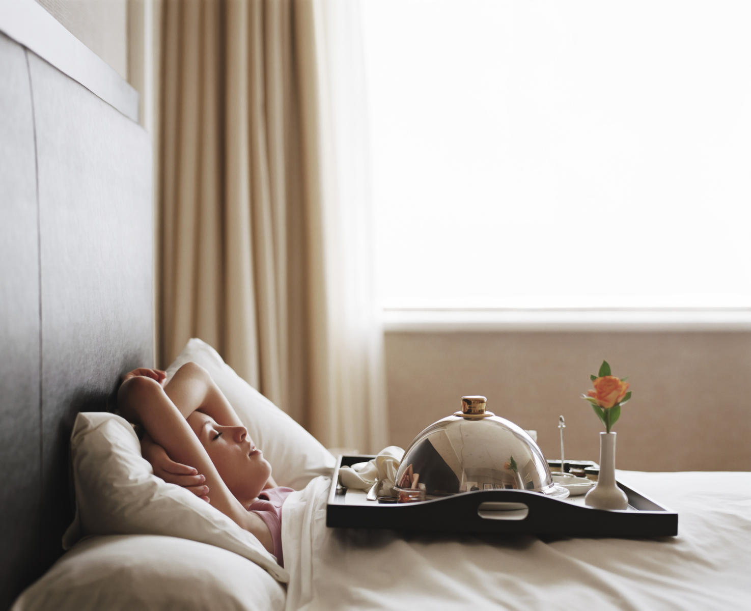 Woman lying in hotel bedroom with tray on chest, eyes closed