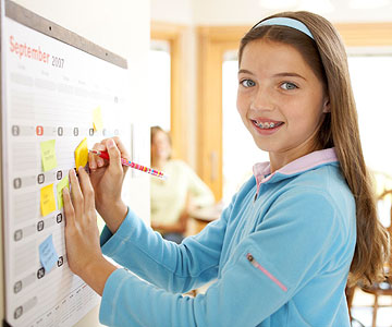 girl penciling in on calendar