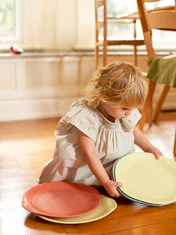 Little girl picking up dinner plates