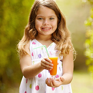 child holding orange carrot and OJ drink
