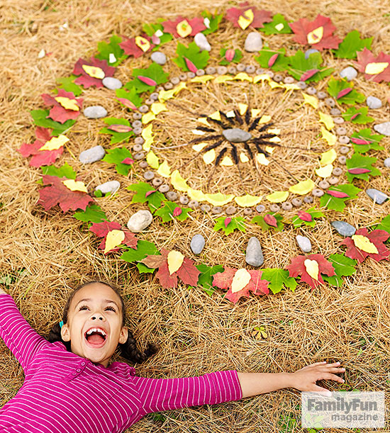 Smiling girl lying below a mandala made of natural materials