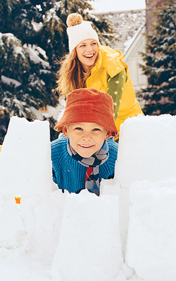 Mom and son behind a snow fort