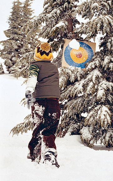 Boy throwing snowball at target