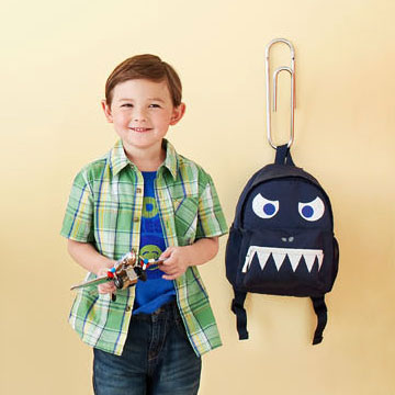 Child standing next to backpack
