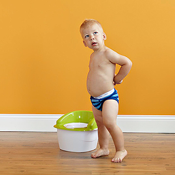 child next to potty training toilet