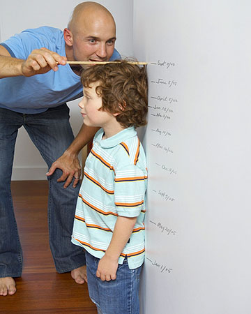 father measuring son's height