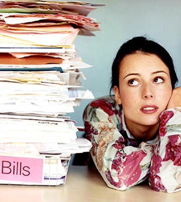 A woman eyeing a towering stack of bills next to her.
