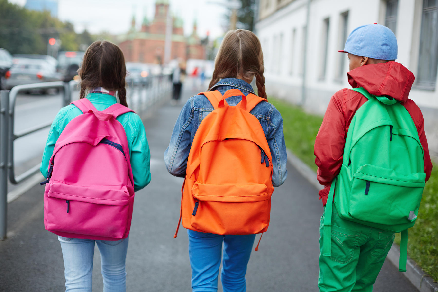 children walking home from school with colorful backpacks