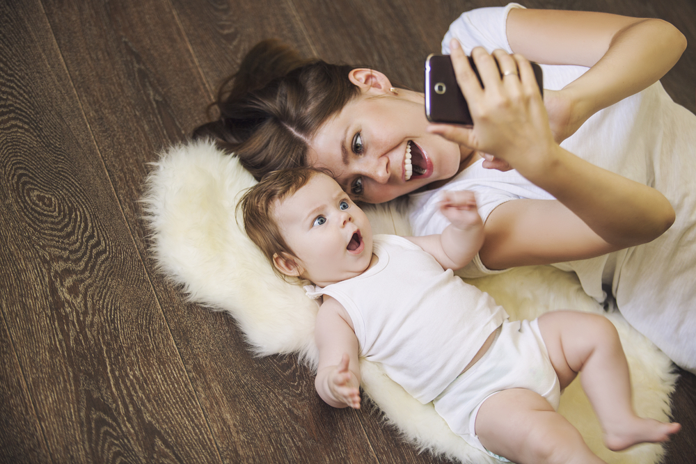 Mom with toddler looking at cellphone