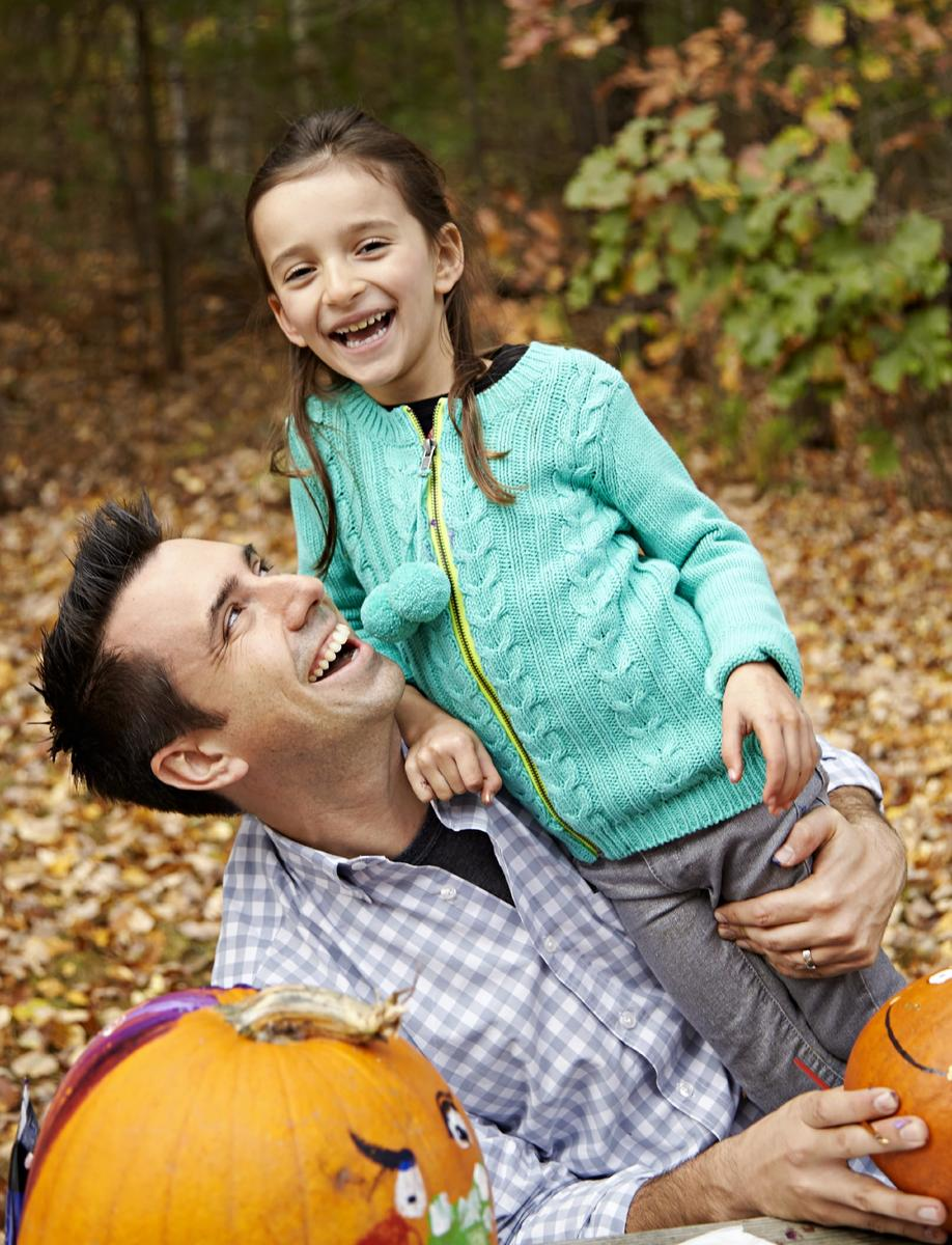Dad and Daughter Smiling with Pumpkin