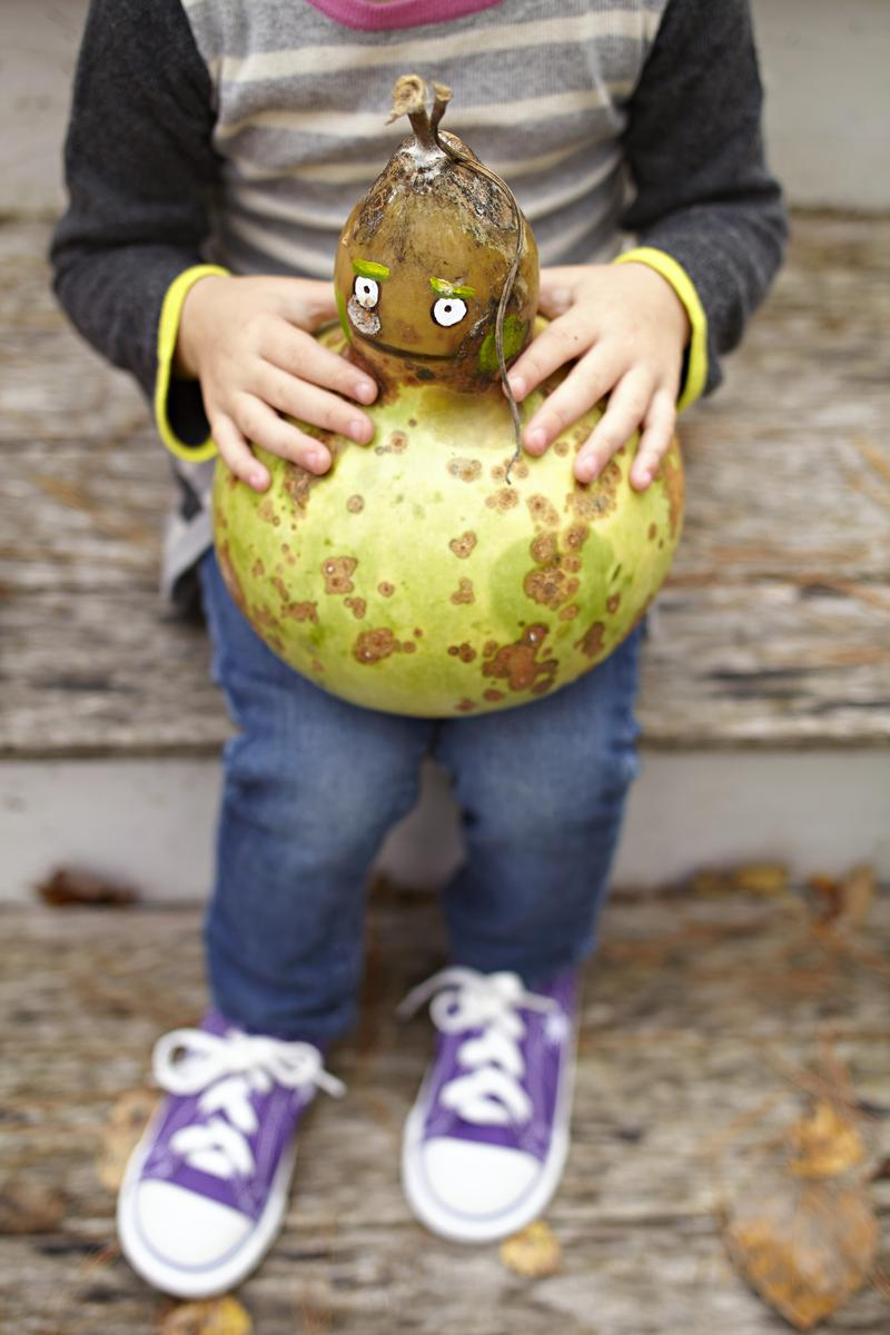 Girl Holding Decorated Pumpkin Gourd