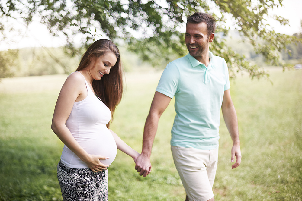 smiling pregnant couple holding hands outside