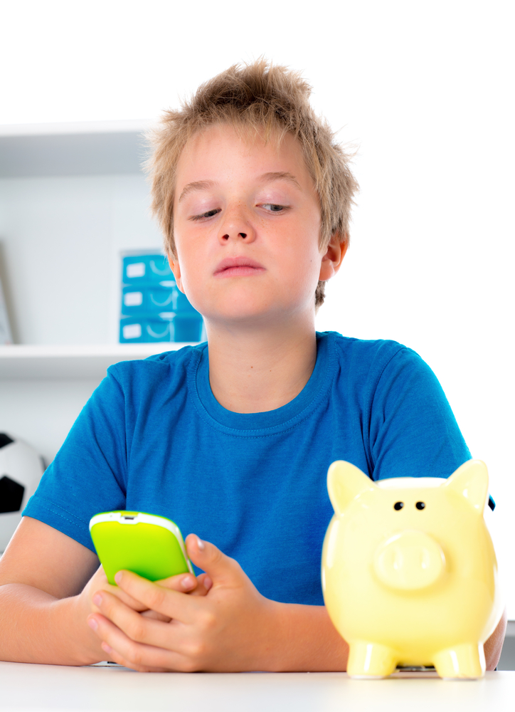 Boy glancing at piggy bank with phone in hand