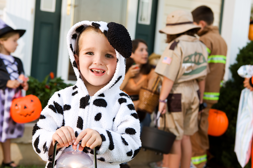Child in halloween costume holding goody bag