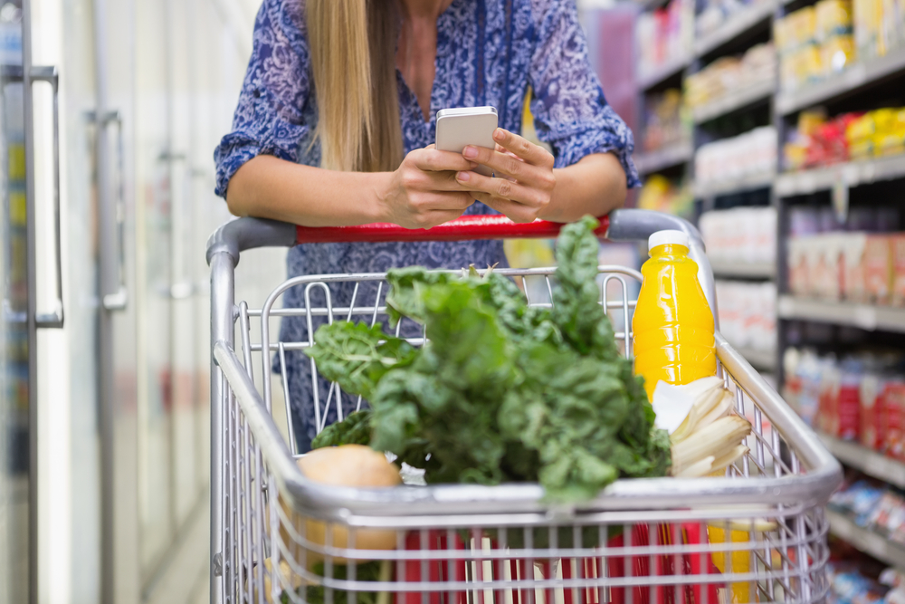 Woman on smartphone at grocery store