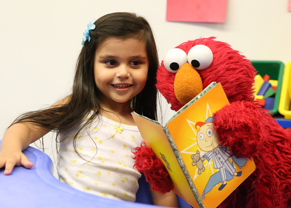 Elmo reading to autistic young girl