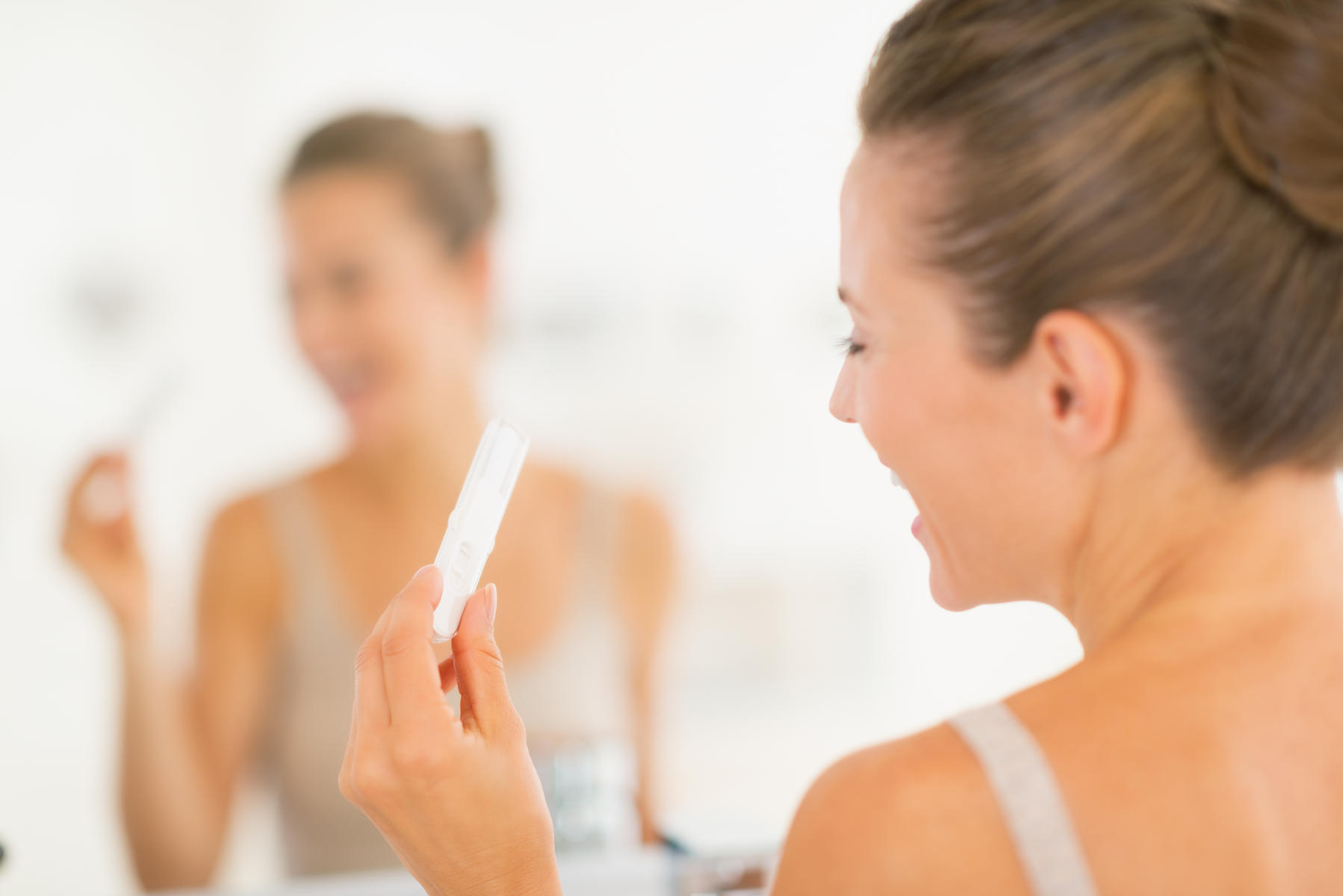 happy woman looking at pregnancy test