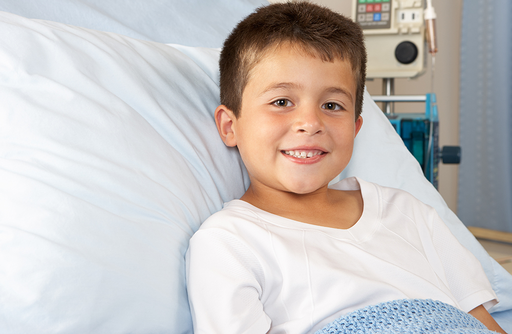 smiling boy in hospital bed