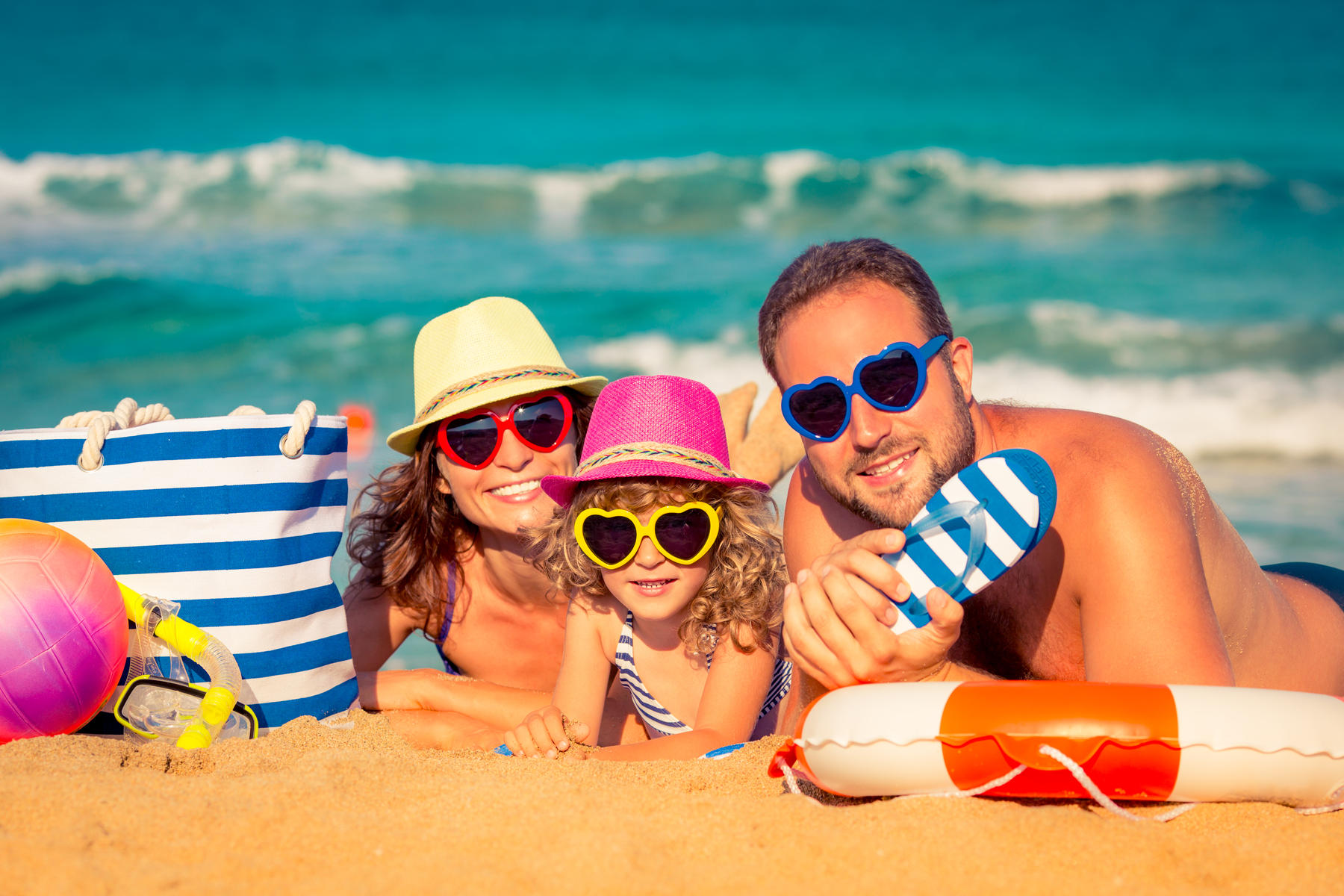 Family at the beach wearing heart-shaped sunglasses