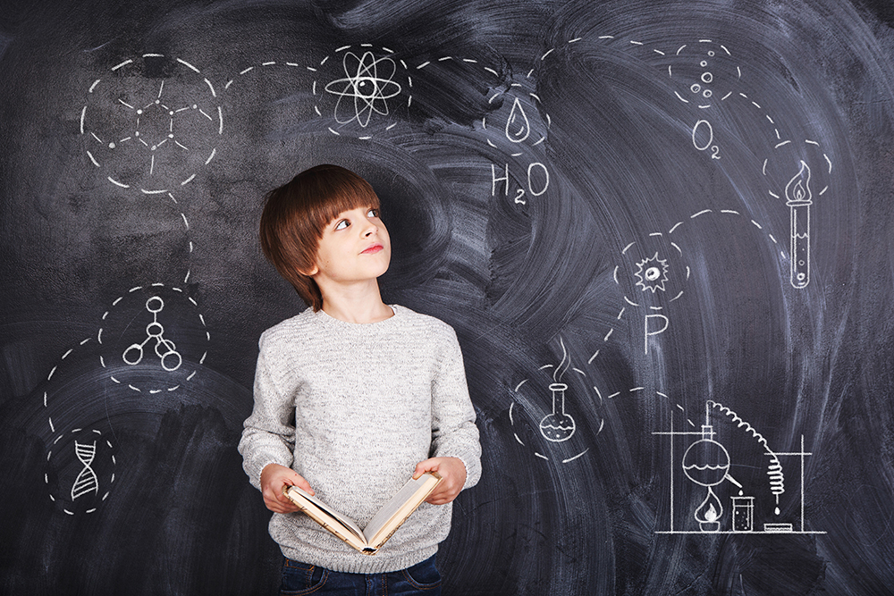 Boy thinking against black chalkboard backdrop