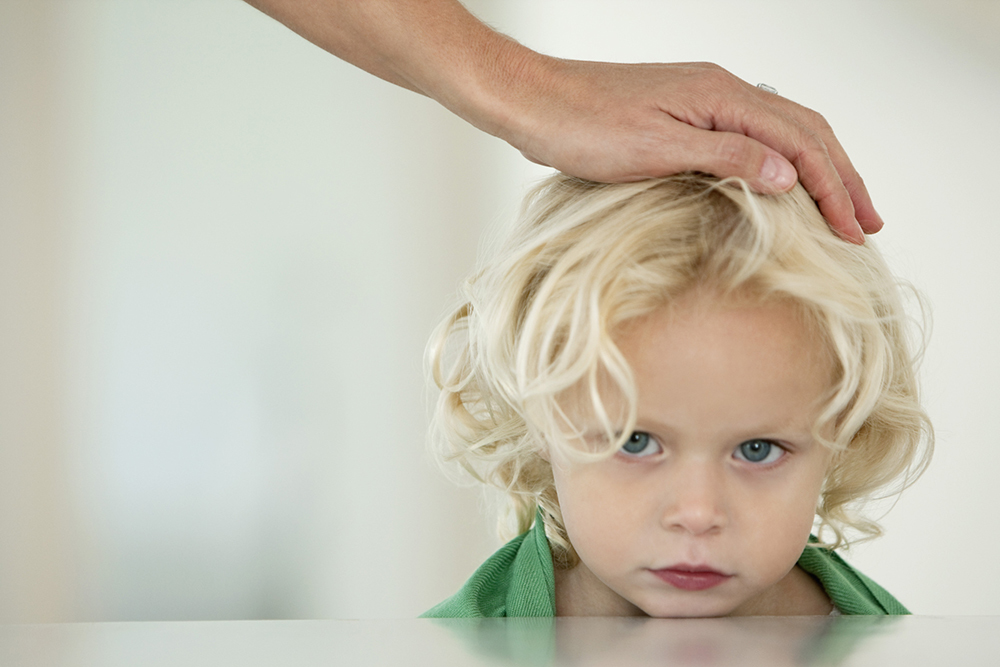 womans hand on childs head