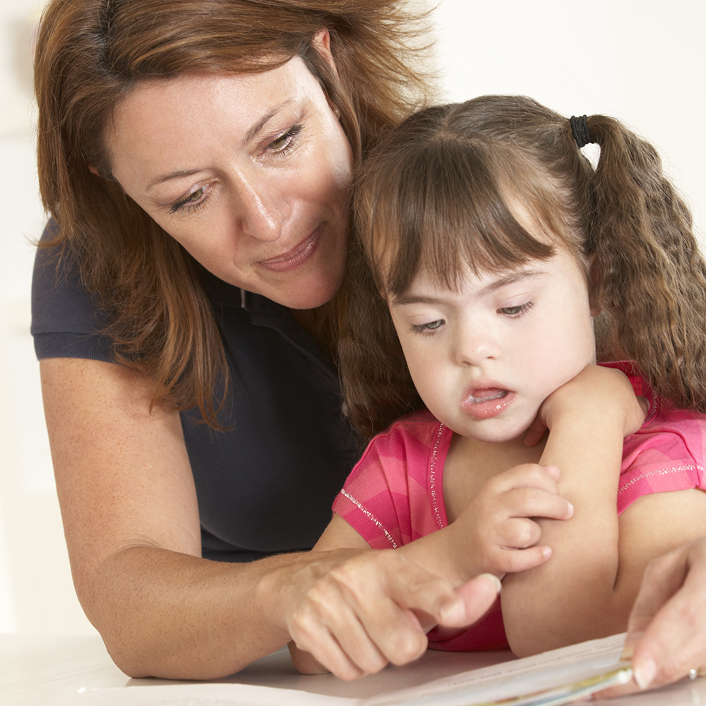 mom and daughter with down syndrome reading together