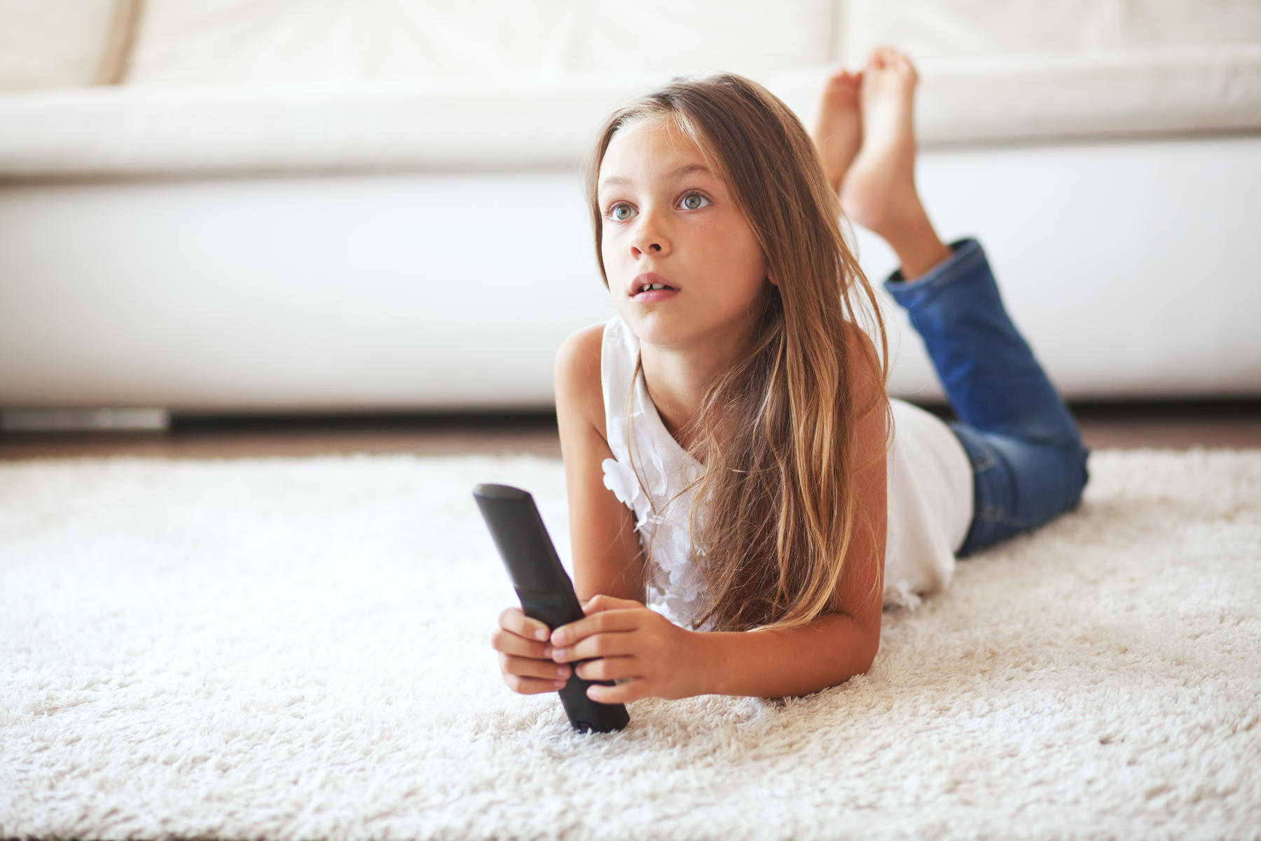 Young girl on the floor watching TV