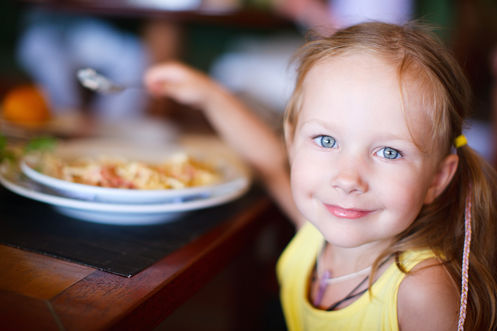 little girl eating at restaurant