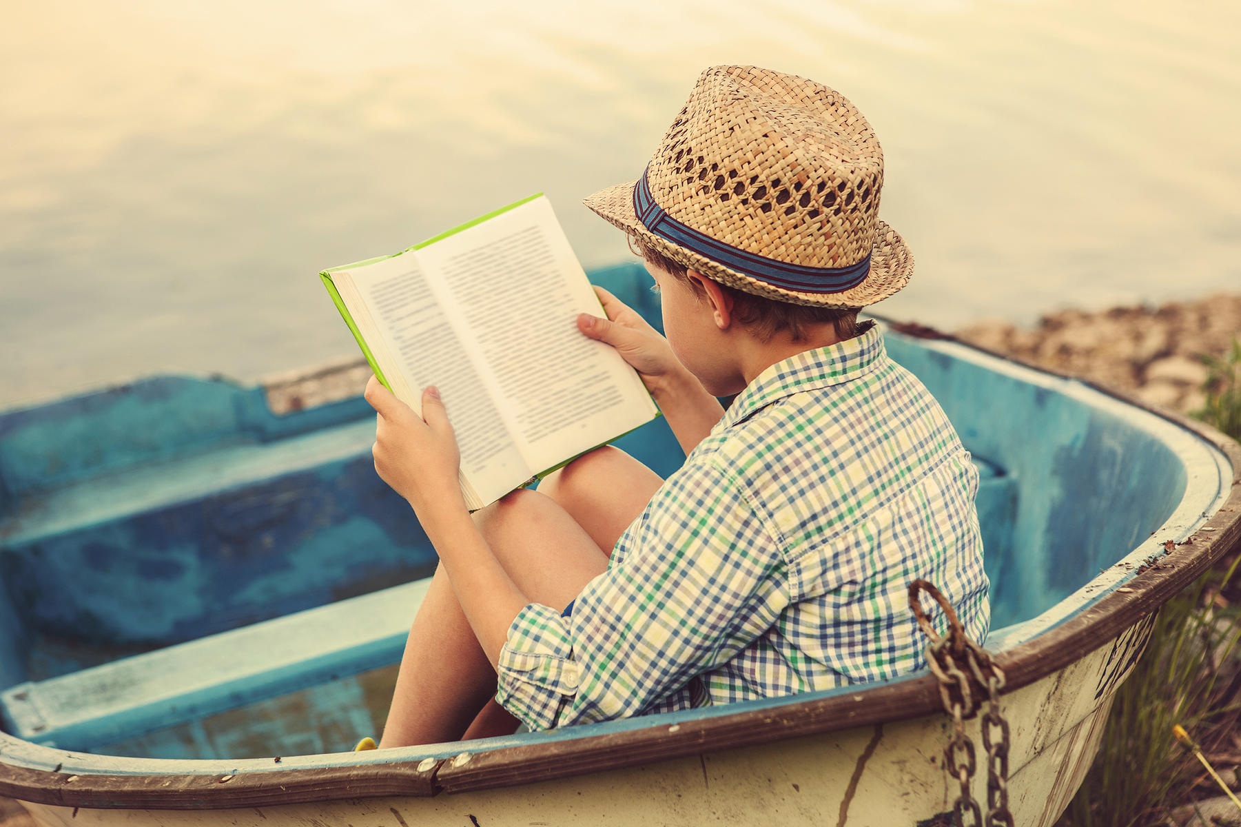 Summer Reading: Boy Reading a Book in a Boat