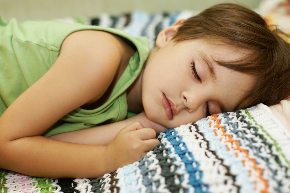 Boy sleeping on colorful striped blanket