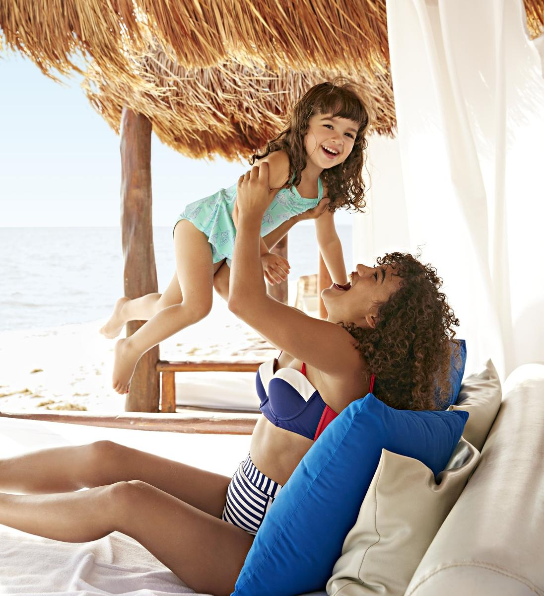 Mom with Curly Hair Holding Daughter in a Cabana