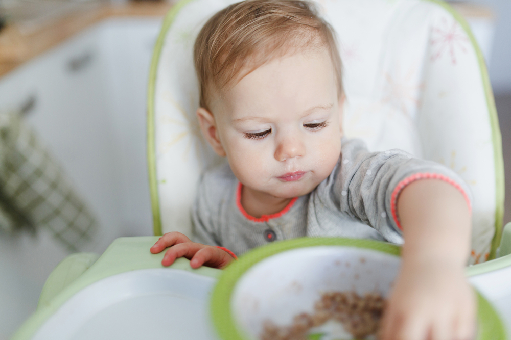 little girl eating in high chair