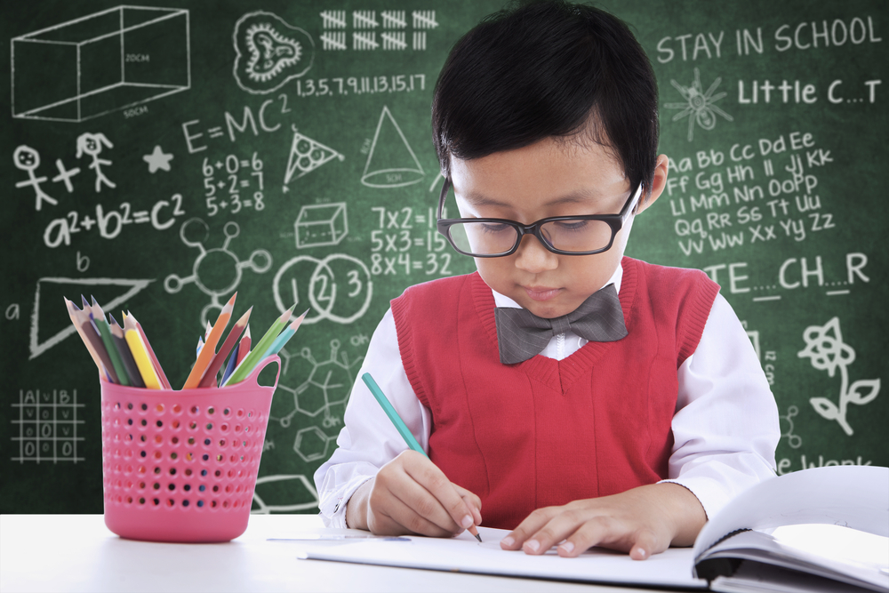 Asian Boy in Glasses Doing Homework