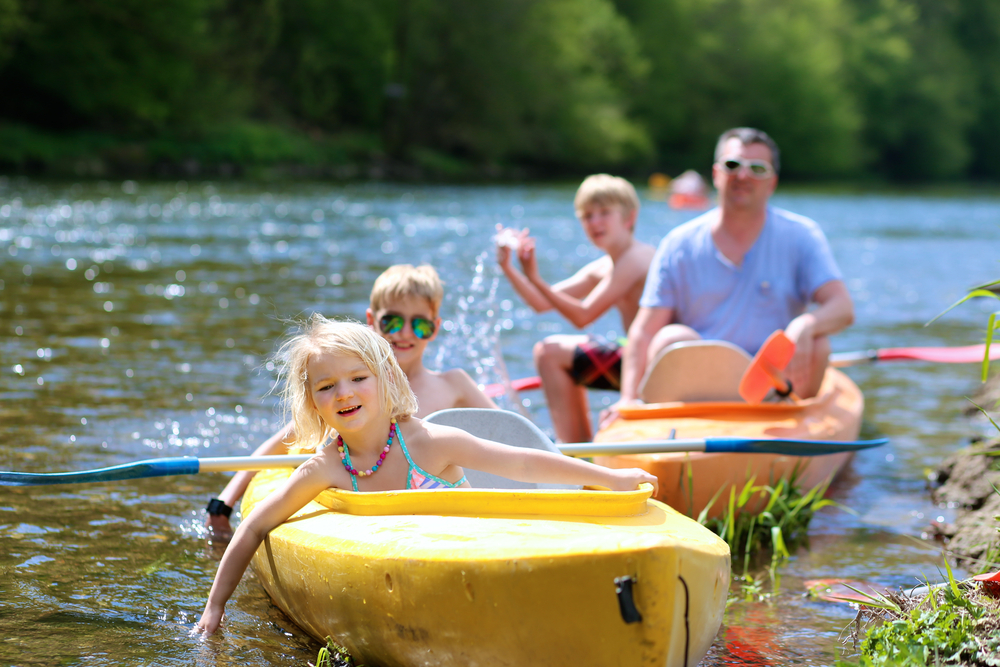 family kayaking on the river
