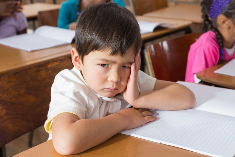 upset boy sitting in classroom
