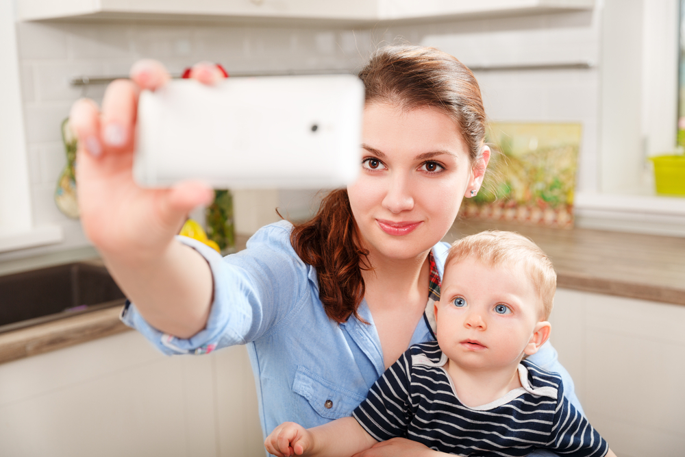 Babysitter and child using social media on cell phone