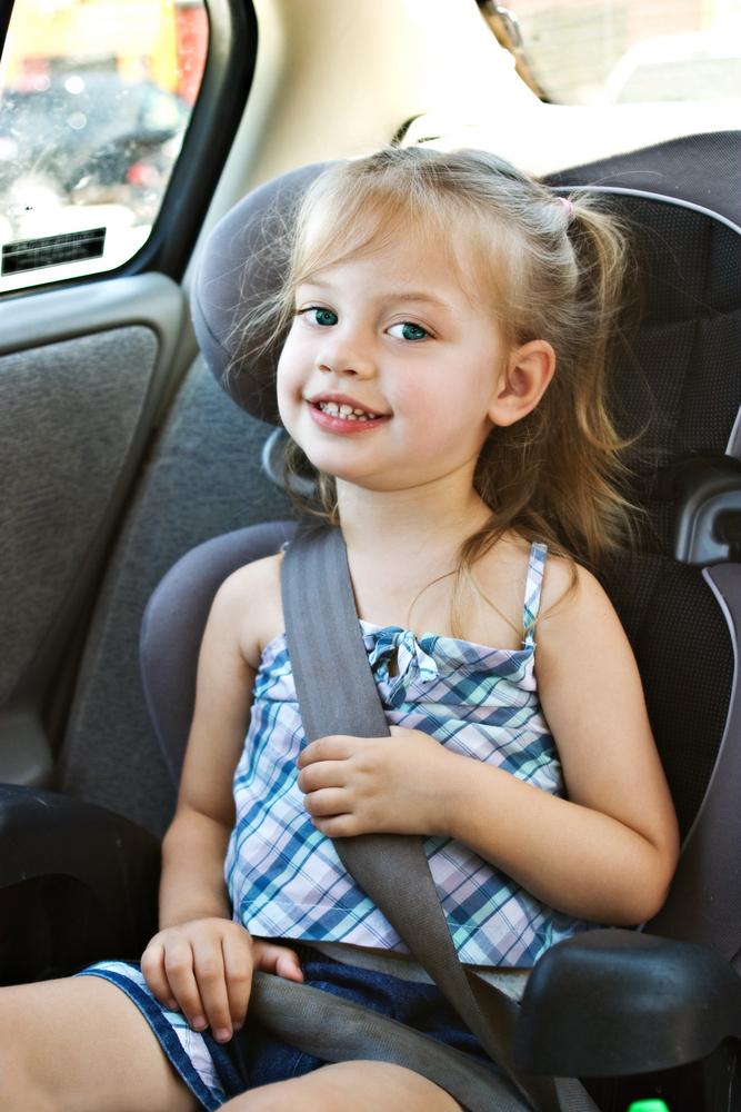 smiling girl in car booster seat