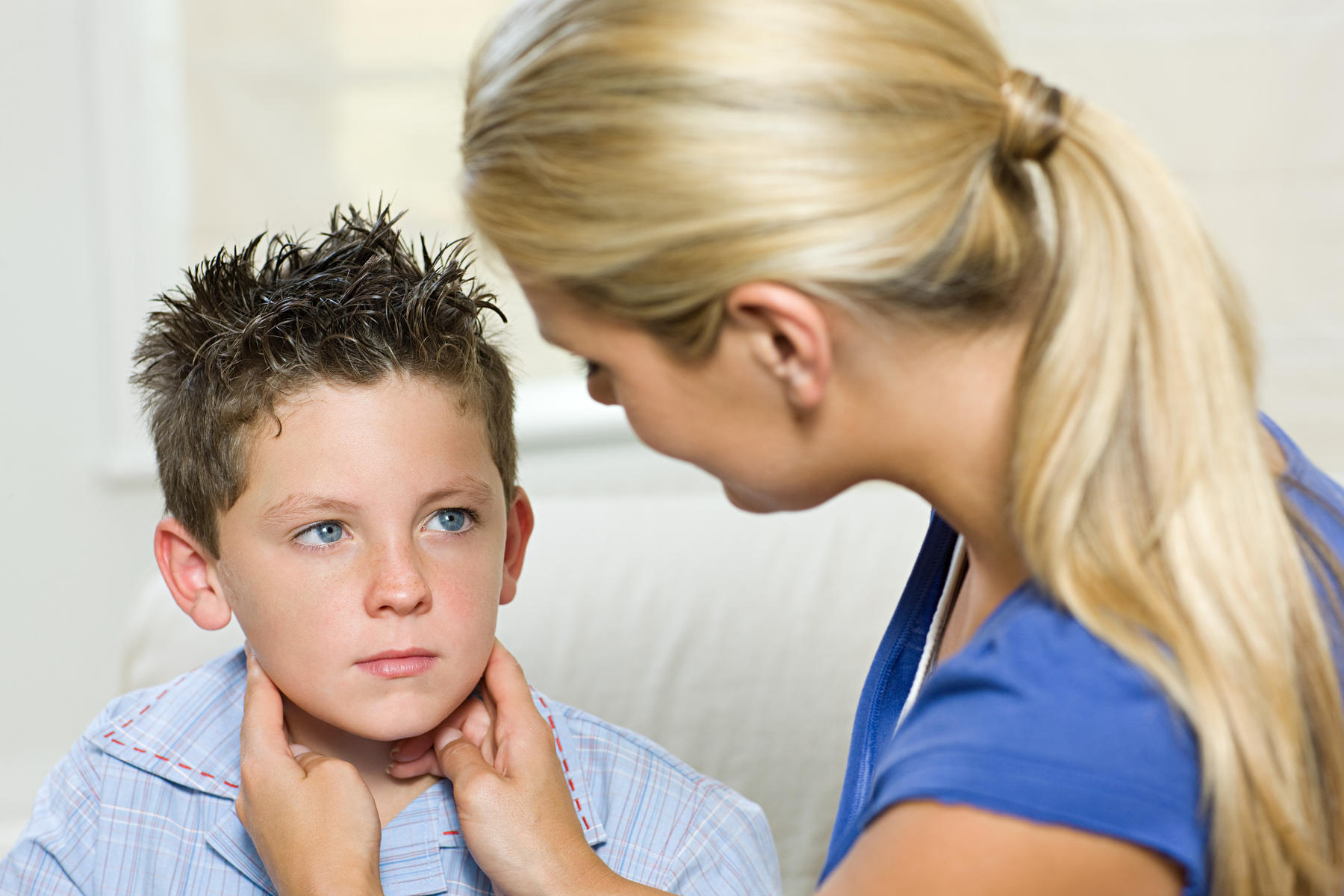 mother feeling son's neck for mumps