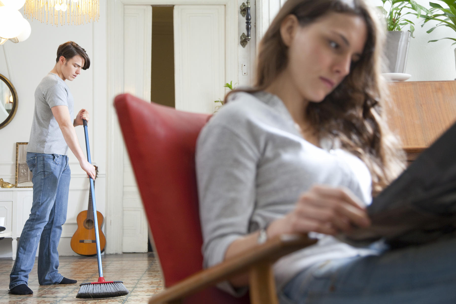man sweeping while woman reads