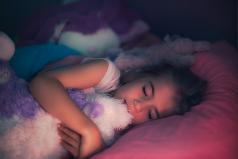 little girl sleeping in bed with stuffed animal