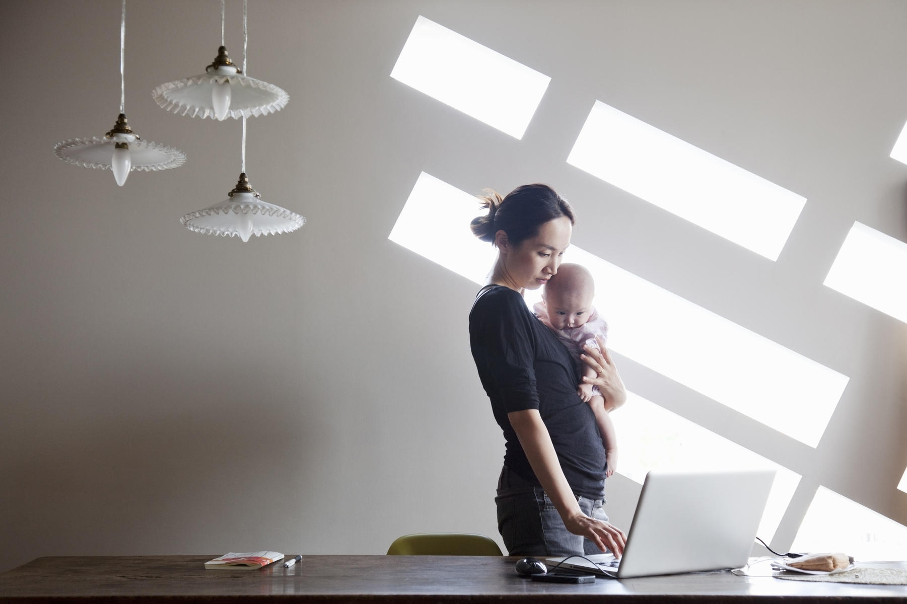 new mother starting a business from home, holding baby