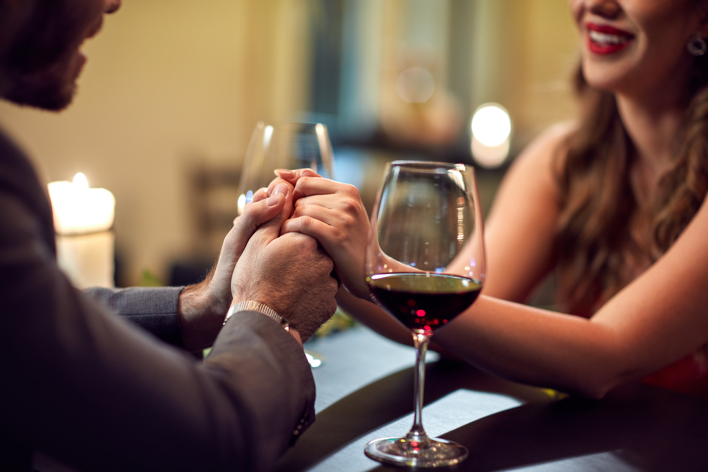 Date Night Red Wine and Couple Hold Hands