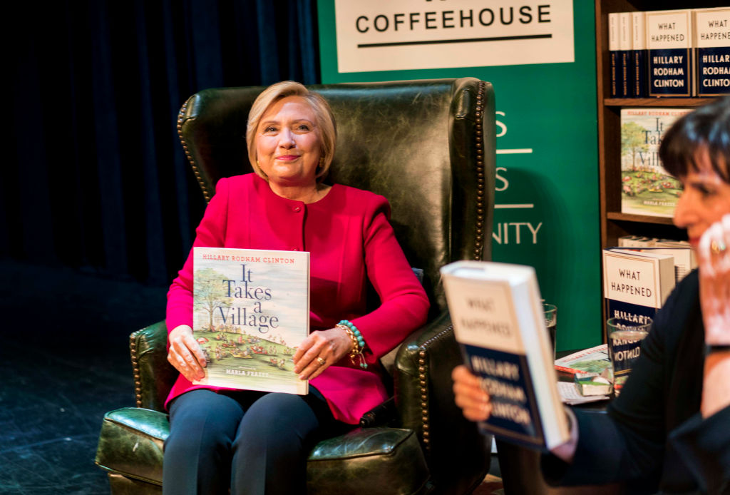 "Former Secretary of State Hillary Clinton holds her children's book ""It takes a Village"""