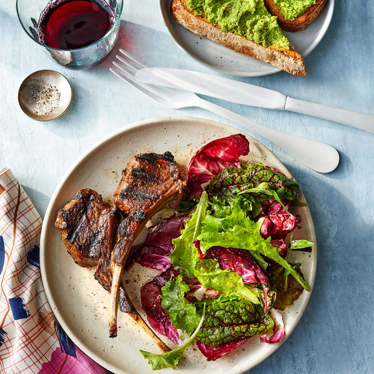 Lamb Chops With Mashed Peas on Toast on neutral plates with silverware glass and napkin
