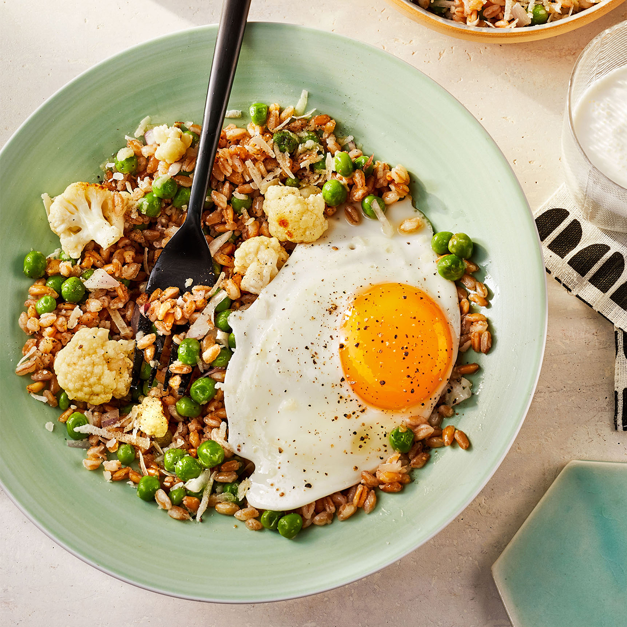 Veggie Farrotto With Sunny-Side-Up Eggs on green plate with fork