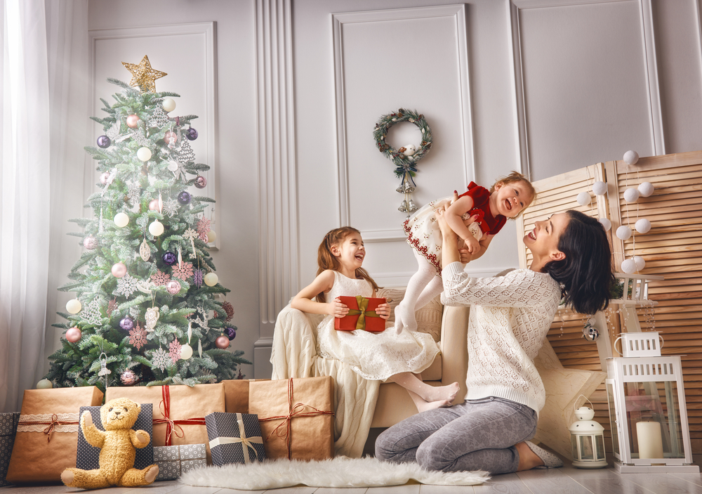 Happy Woman and Children By The Christmas Tree